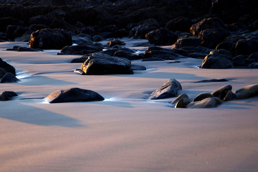 Shadowed Rocks on Smooth Sand Beach