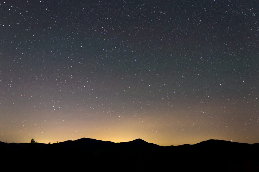 Starry Night Sky and Mountain Silhouettes