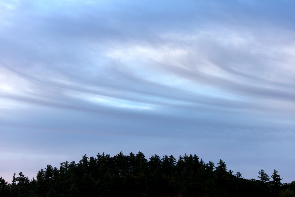 Swirling Clouds Over Hill